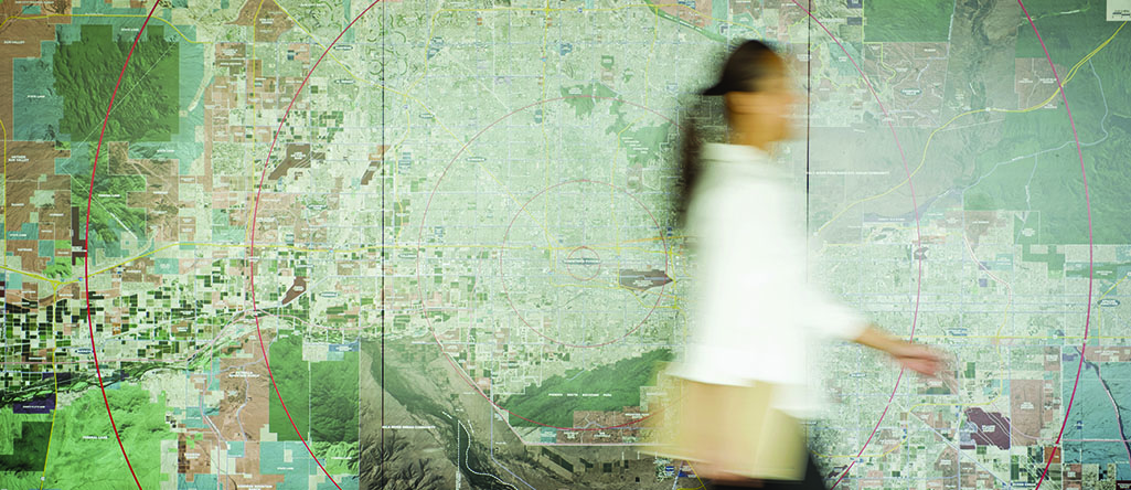 Mixed race businesswoman walking in conference table with map in background