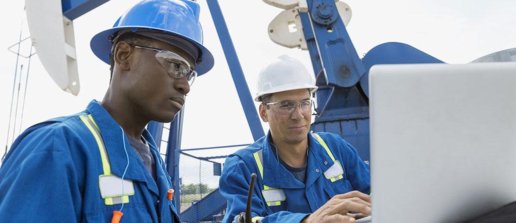 Male workers using laptop below oil well