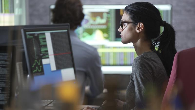 Stock photo of a good looking man &  woman working in an office surrounded by large computer monitors.